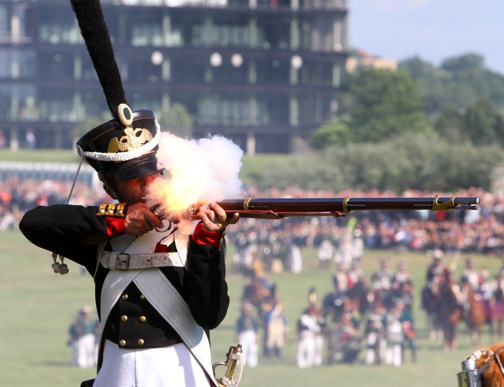 Un bărbat îmbrăcat în uniformă militară trage cu puşca sa în timp ce ia parte la o reconstituire istorică a atacului armatelor conduse de Napoleon Bonaparte, la 24 iunie 1812, asupra Rusiei ţariste, în Kaunas, Lituania, sâmbătă, 23 iunie 2012.