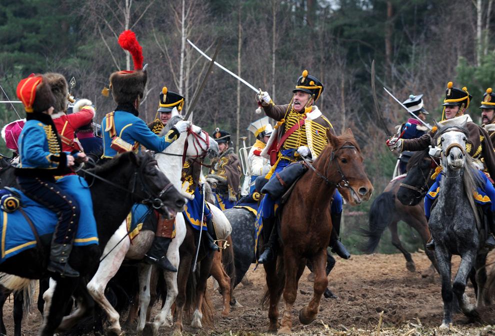 Pasionaţi de istoria militară îmbrăcaţi în uniforme militare franceze şi ruseşti din timpul războaielor napoleoniene reconstituie o bătălie pentru a marca cea de-a 200-a aniversare a retragerii din Rusia, peste râul Berezina, a armatelor conduse de Napoleon Bonaparte, în apropierea satului Studenka, în Belarus, sâmbătă, 24 noiembrie 2012.