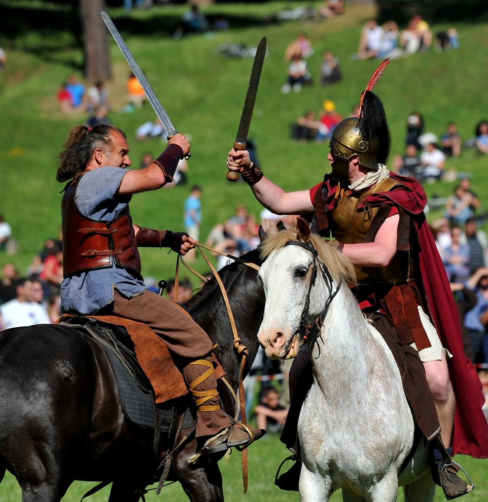 Actori îmbrăcaţi precum soldaţii romani şi barbarii din perioada Romei antice reconstituie o luptă pentru a marca bătălia dintre Marcus Aurelius şi Ballomar, la Vila Pamphili din Roma, duminică, 19 mai 2013.