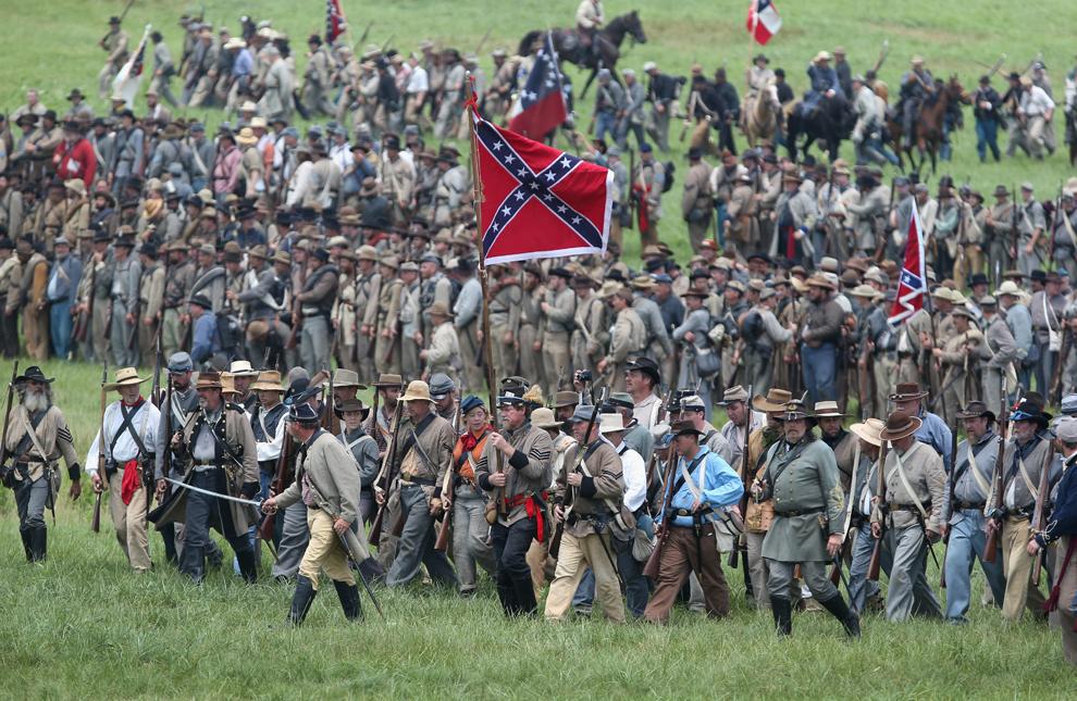 Participanţi la reconstituirea bătăliei de la Gettysburg din timpul Războiului Civil American, îmbrăcaţi în uniforme confederate, mărşăluiesc către liniile unioniste în timpul reconstituirii asaltului generalului Pickett, în ultima zi a evenimentului, în Gettysburg, Pennsylvania, Statele Unite, duminică, 30 iunie 2013.