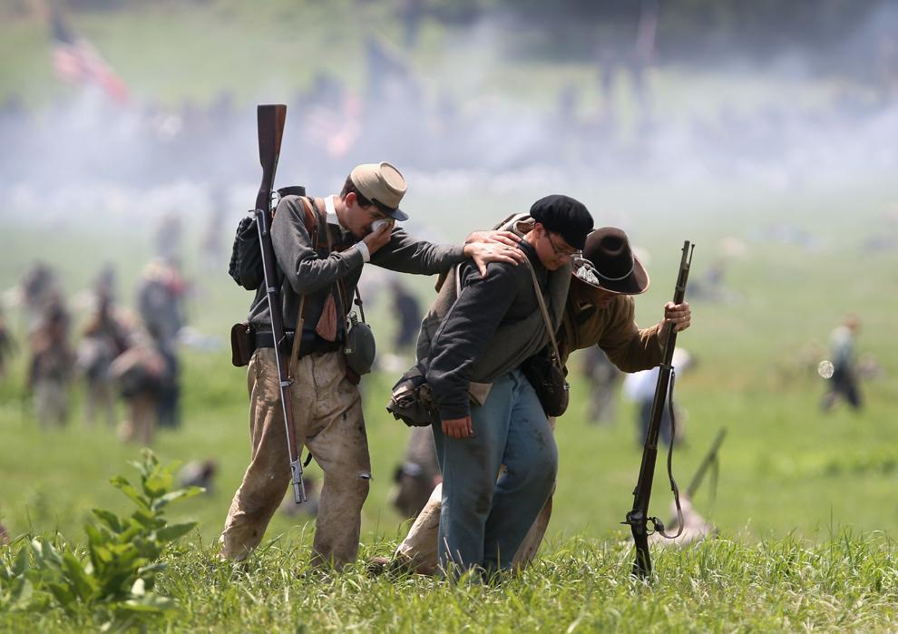 Participanţi la reconstituirea bătăliei de la Gettysburg din timpul Războiului Civil American, îmbrăcaţi în uniforme confederate, se retrag la finalul reconstituirii asaltului generalului Pickett, în ultima zi a evenimentului, în Gettysburg, Pennsylvania, Statele Unite, duminică, 30 iunie 2013.