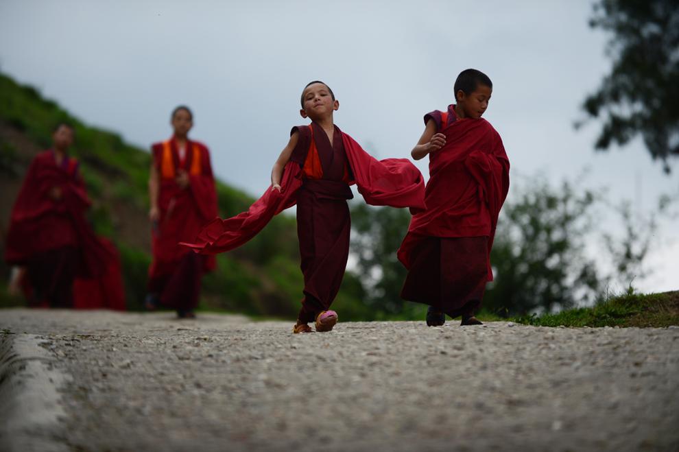 Călugărul discipol în vârstă de 6 ani, Tandi Dorji (C), merge la micul dejun, la o mânăstire din Thimpu, capitala Bhutanului, luni, 3 iunie 2013.