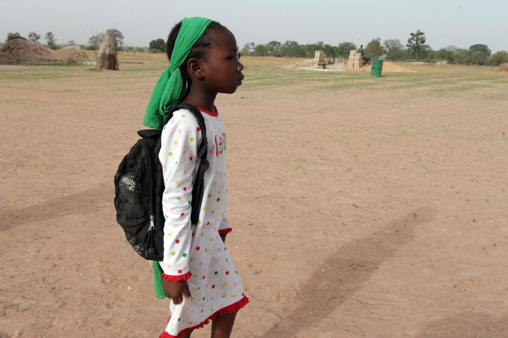 Ndeye Fatou Ndiaye, 7 ani, din Senegal, soseşte acasă de la şcoală, în Diagnel, 14 km sud de Kaolack, în centrul Senegalului, luni, 10 iunie 2013.