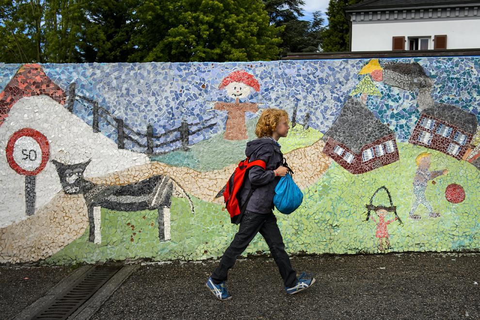 Leon, 9 ani, merge la şcoală pe lângă un zid decorat, în oraşul Moudon, vestul Elveţiei, joi, 20 iunie 2013.
