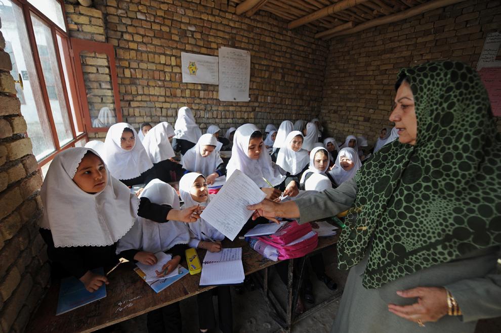 O profesoară afgană întinde o foaie de hârtie unei eleve, în şcoala primară din Mazar-i-Sharif, Afganistan, vineri, 12 aprilie 2013.