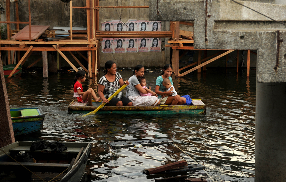 Femei călătoresc alături de copii cu barca pentru a se întoarce la casele lor din oraşul Malabon, Manila, miercuri, 5 iunie 2013.