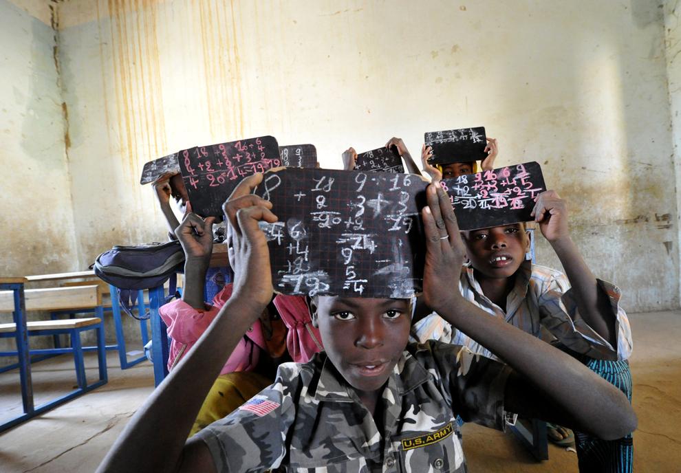 Elevi ridică tabliţele pe care au scris, într-o sală de clasă din care au fost luate mesele si bancile de catre islamisti, în prima zi in care au fost redeschise scolile, în Gao, Mali, luni, 4 februarie 2013.