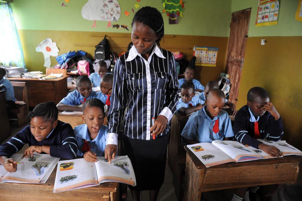 Cadrul didactic Bosede Omoniyi (C), îl ajută pe Omoze Ogwogho ( al II-lea din D), 7 ani, în timpul unei ore de curs, la şcoala Internaţională Christower, în Nigeria, joi, 6 iunie 2013.