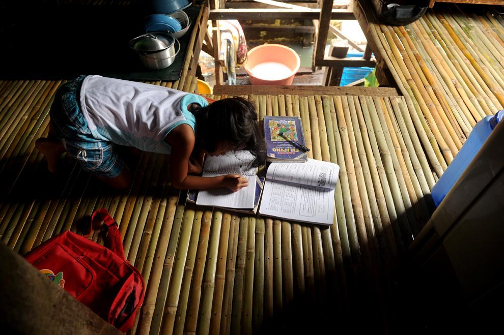 Genesis Tuazon, 8 ani, elevă în clasa a treia la şcoala primară Pangulo, îşi face temele acasă, în oraşul Malabon, lângă Manila, Filipine, vineri, 14 iunie 2013.