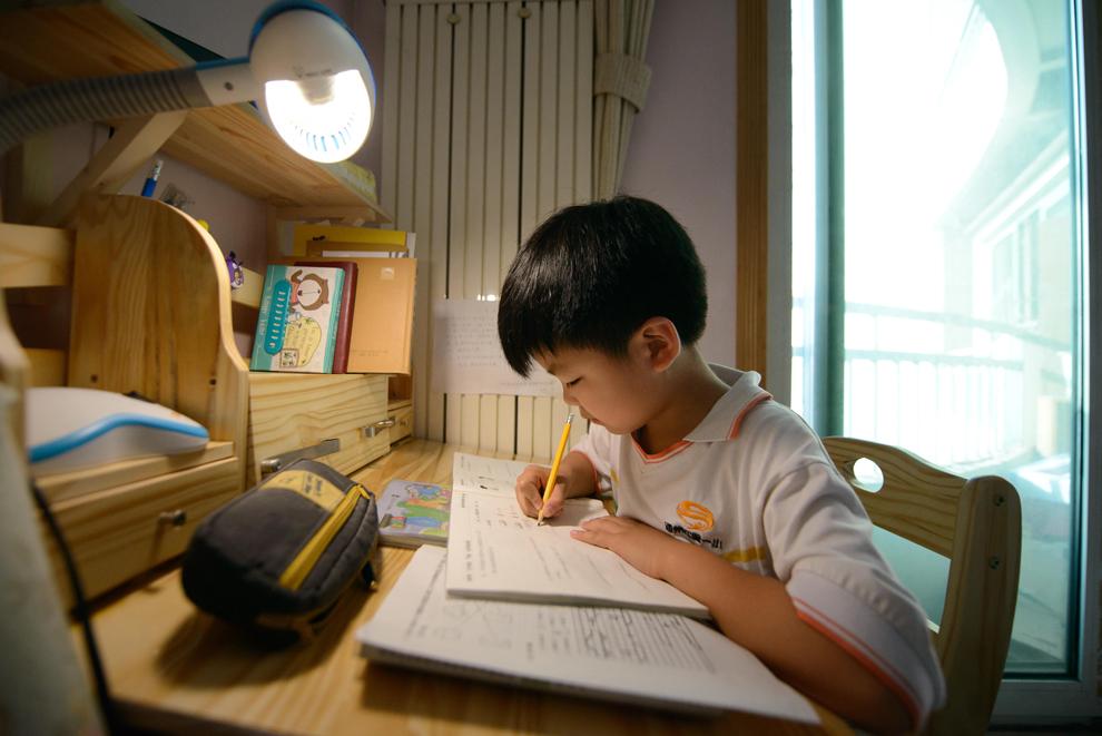 Wei Hanqi, 9 ani, îşi face temele de casă, în Beijing, miercuri, 19 iunie 2013.