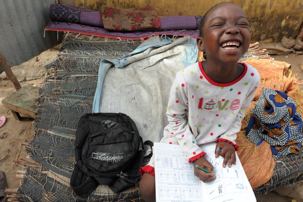 Ndeye Fatou Ndiaye, 7 ani, din Senegal, râde în timp ce îşi face temele de casă, în Diagnel, 14 km sud de Kaolack, în centrul Senegalului, luni,  10 iunie 2013.