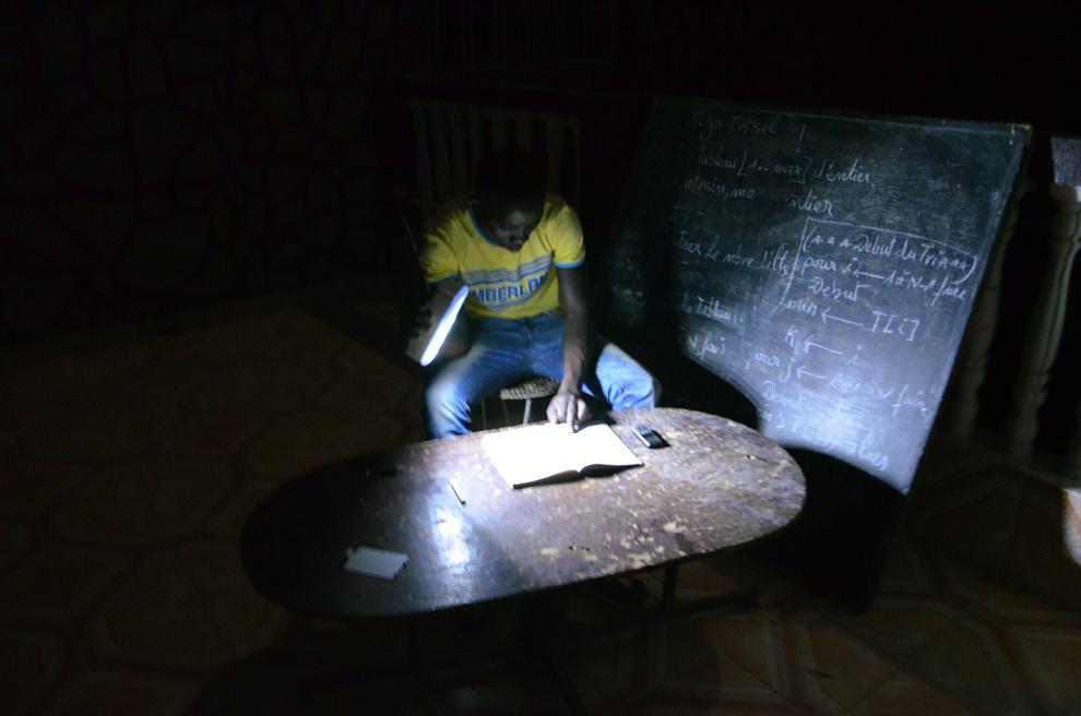 Un elev îşi face temele la lumina lanternei, în timpul unei pene de curent în oraşul Niamey, Niger, marţi, 18 iunie 2013.