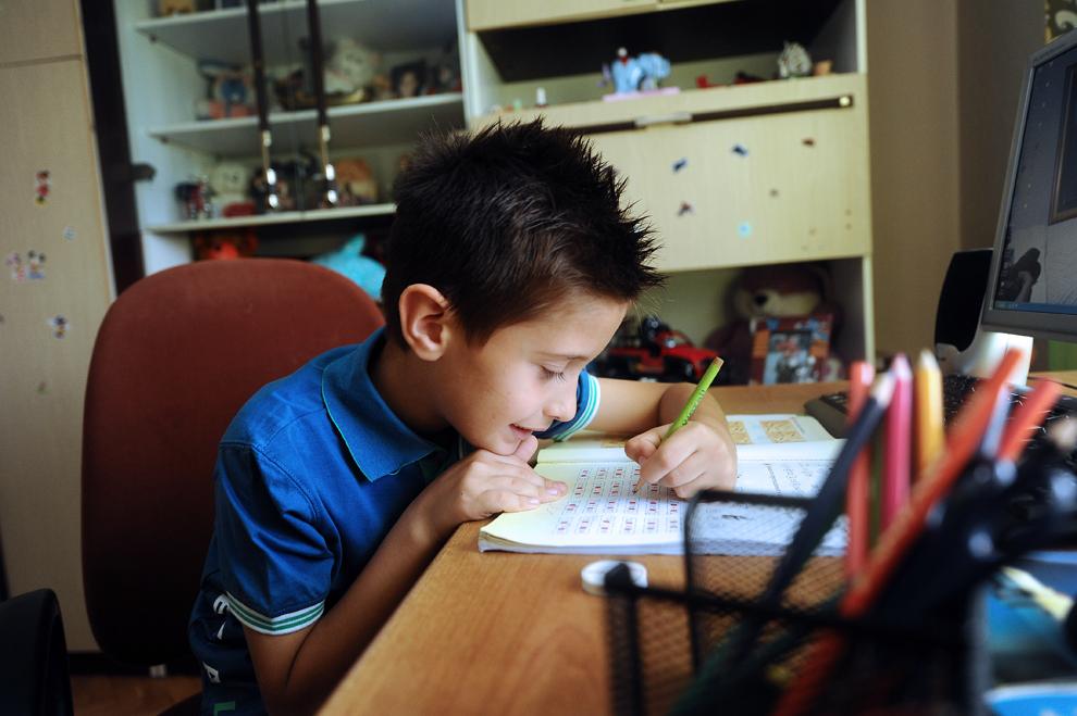 Viktor Stefanovic, 7 ani, îşi face temele de casă, în Skopje, Macedonia, miercuri, 5 iunie 2013.
