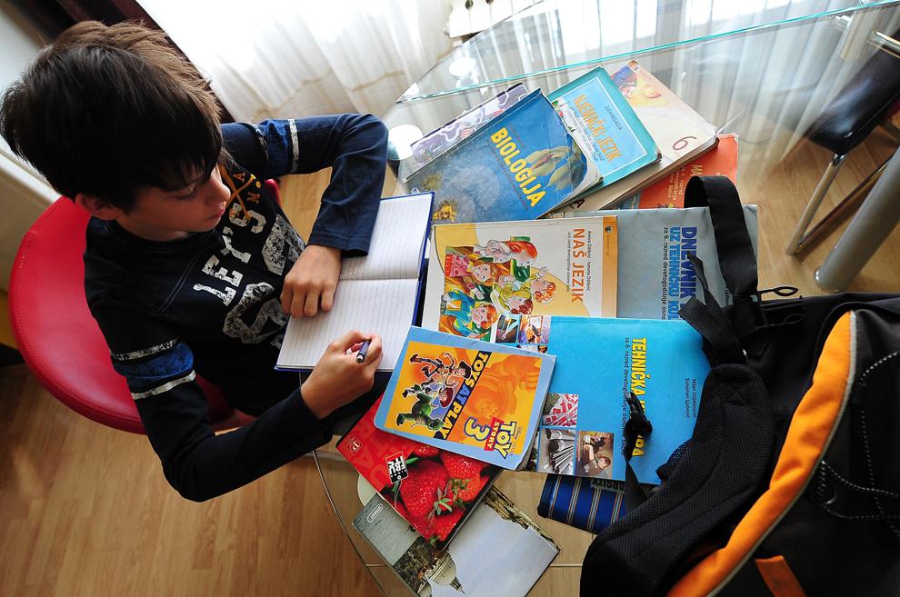 Un băiat bosniac, Aldemar Alikavazovic, 12 ani, îşi face temele acasă, într-o suburbie a oraşului Sarajevo, joi, 27 iunie 2013.