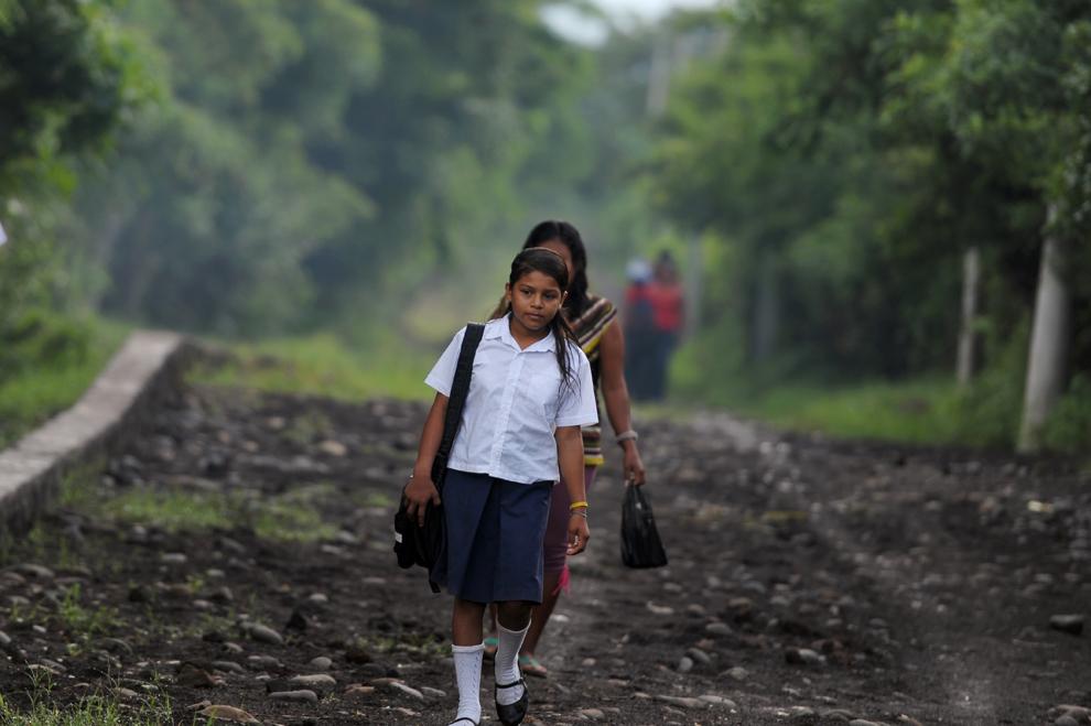 Silvia Alvarado (D), 10 ani, merge la şcoală, în satul Metalio, lângă oraşul Acajutla, la sud de San Salvador, luni, 1 iulie 2013.