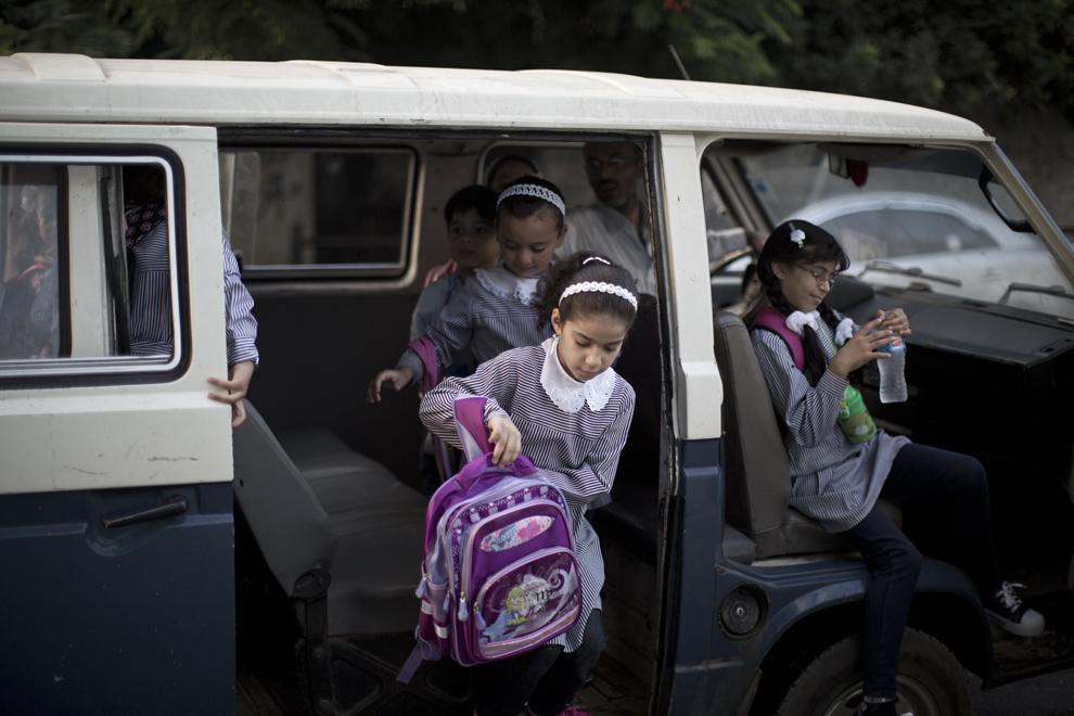 Elevi palestinieni coboară dintr-un microbuz, în faţa şcolii, în prima zi a noului an şcolar, în Gaza, Palestina, luni, 26 august 2013.