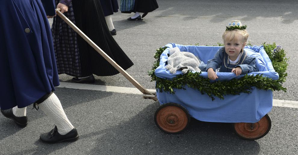 Theresa stă într-un cărucior, în timp ce participă la parada costumelor tradiţionale bavareze, în timpul festivalului berii, Oktoberfest, în Munchen, Germania, duminică, 22 septembrie 2013.