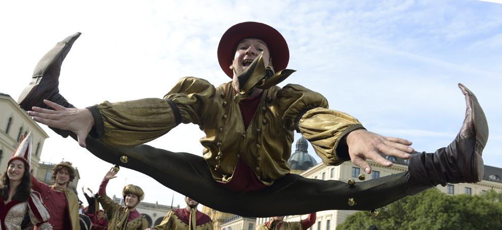Un acrobat sare în timp ce participă la parada costumelor tradiţionale bavareze, în timpul festivalului berii, Oktoberfest, în Munchen, Germania, duminică, 22 septembrie 2013.