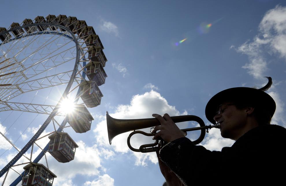 Un muzician cântă în faţa unui carusel, în timpul pregătirilor pentru festivalul Oktoberfest, din Munchen, Germania, joi, 19 septembrie 2013.