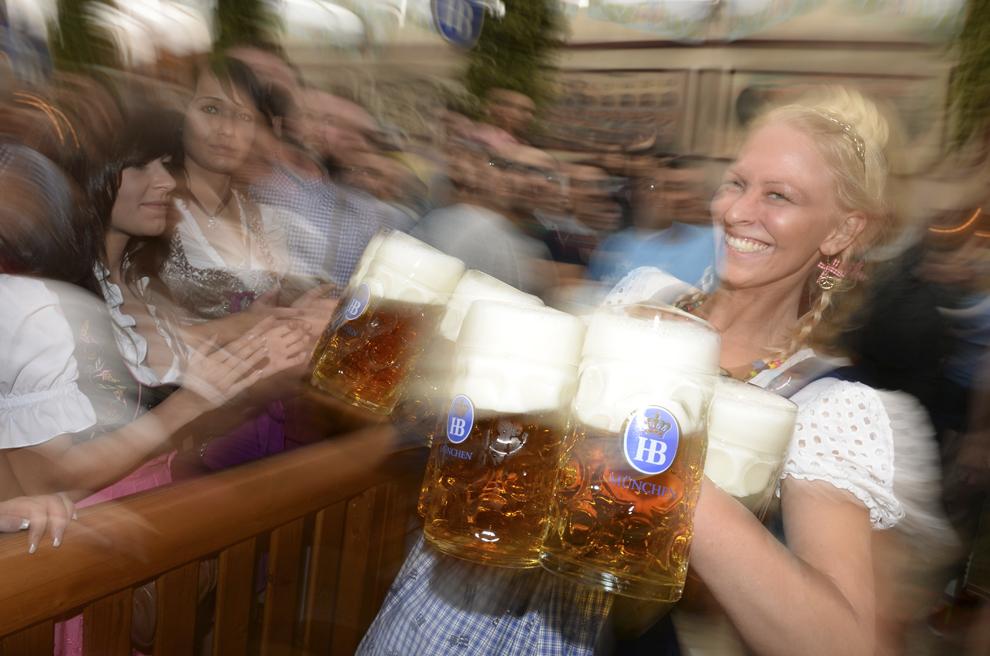 O chelneriţă îmbrăcată în haine tradiţionale bavareze duce mai multe halbe cu bere în timpul deschiderii festivalului berii, Oktoberfest, în Munchen, Germania, sâmbătă, 21 septembrie 2013.