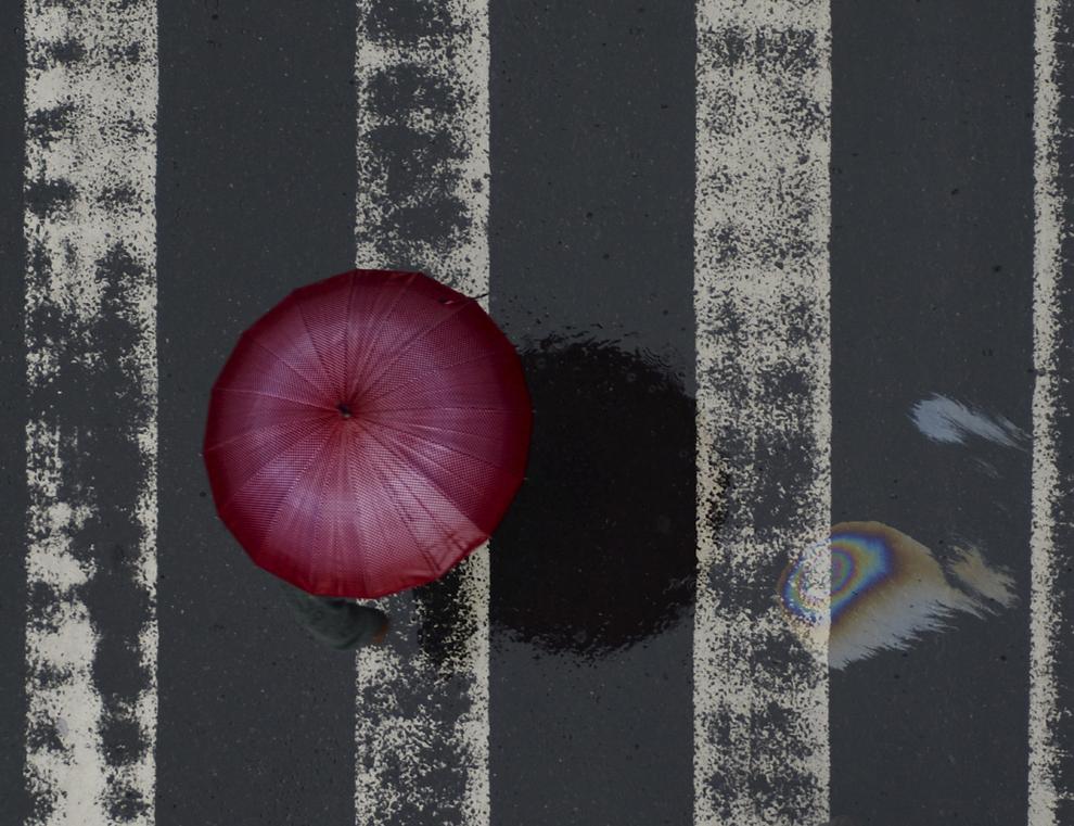 O persoană  traversează o stradă din Rio de Janeiro într-o zi ploioasă, miercuri 4 septembrie 2013.