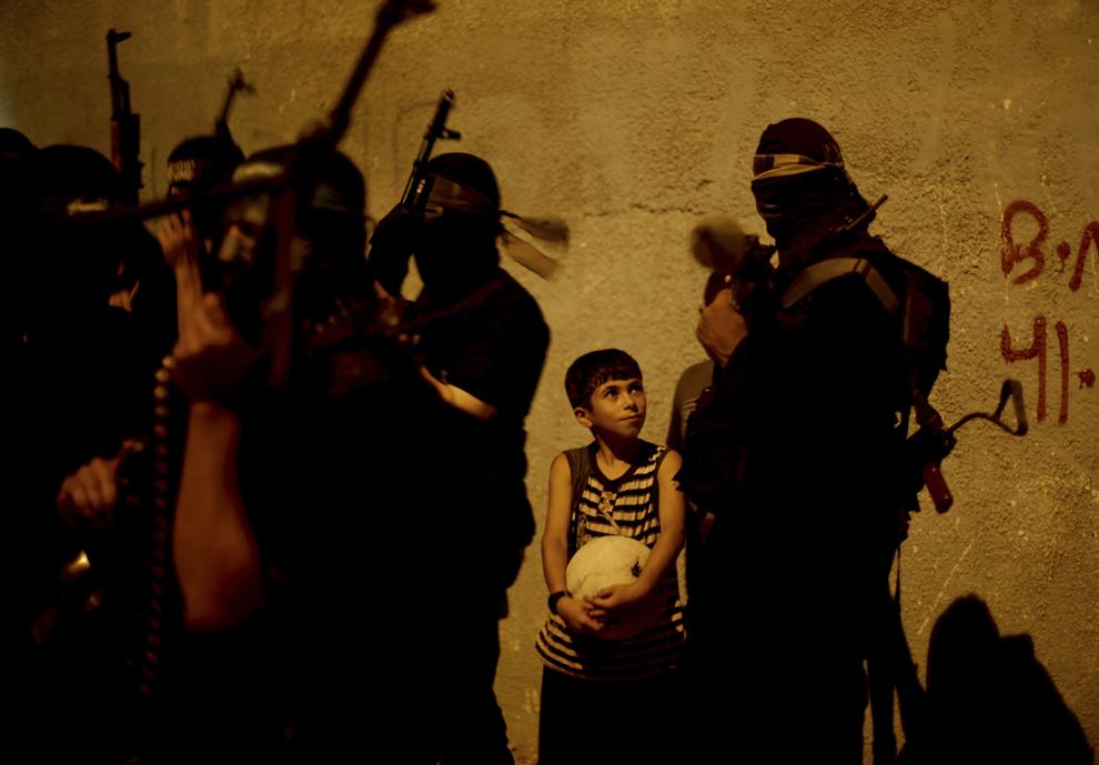 Un băieţel palestian stă lângă un grup de militanţi ai brigăzii militare din mişcarea de rezistenţa Hamas, Ezzeddine al – Qassam, în Gaza City, miercuri, 4 septembrie 2013.