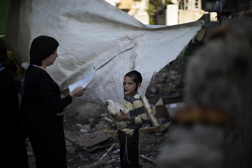 Un baieţel evreu ultra-ortodox ţine în braţe o găină în timp ce o rudă recită o rugăciune, în timpul ceremoniei Kaparot, miercuri, 11 septembrie 2013.