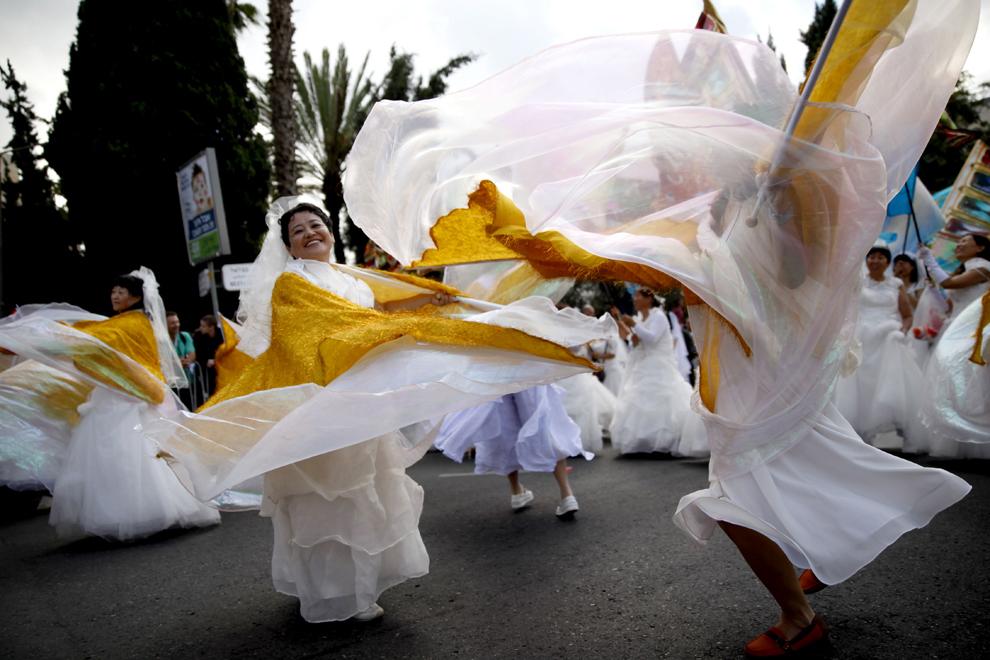 Pelerini creştini evanghelici din China, dansează în timpul unei parade ce celebrează sărbătoarea evreiască de Sukkot, în Ierusalim, marţi, 24 septembrie 2013.