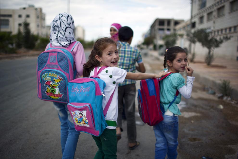 Un grup de copii sirieni ce se îndreaptă către şcoala din districtul Sheikh Najjar, privesc către aparatul de fotografiat, în nordul oraşului Aleppo, luni, 23 septembrie 2013.