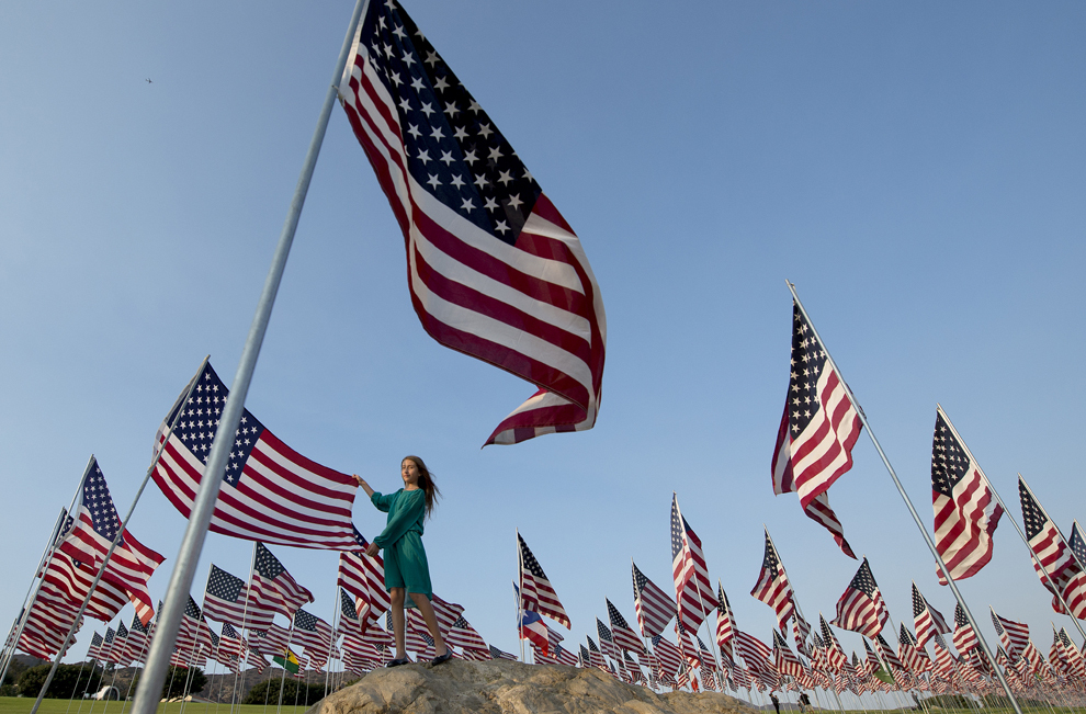 O fată stă lângă steaguri americane ridicate de studenţi şi angajaţi ai universitaţii Pepperdine pentru a comemora victimele atacurilor de la 11 septembrie, în Malibu, California, marţi, 10 septembrie 2013.
