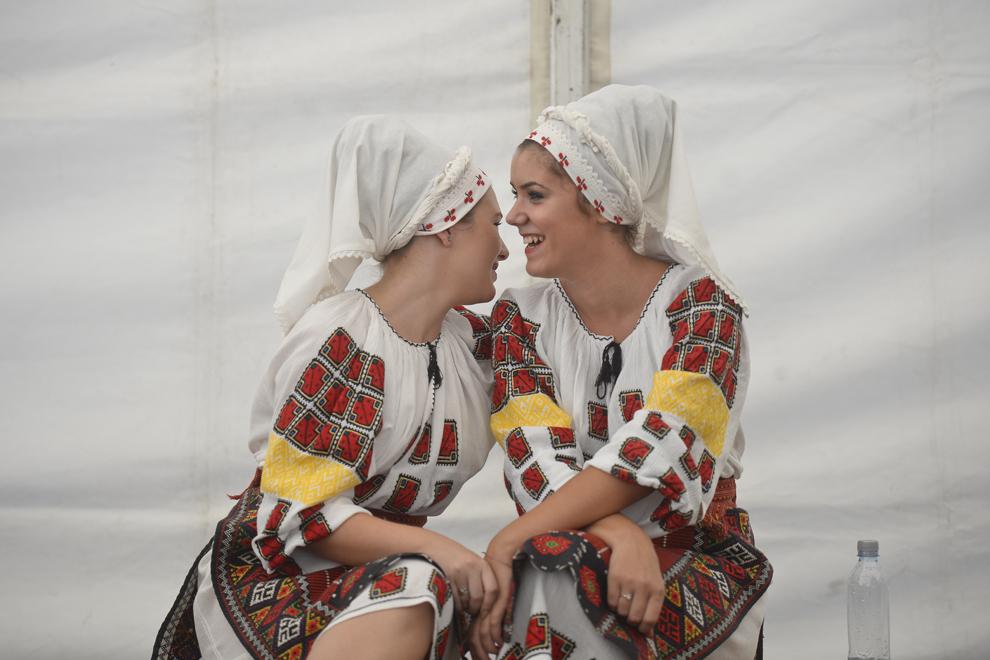 Tinere dintr-un ansamblu folcloric discută înainte de a urca pe scenă, în timpul festivalului Ziua Porumbului, în satul Orezu, judeţul Ialomiţa, joi, 12 septembrie 2013.