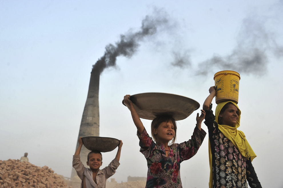 Copii afgani transportă cărbune colectat dintr-o fabrică de cărămizi, în Jalalabad, luni, 9 septembrie 2013.