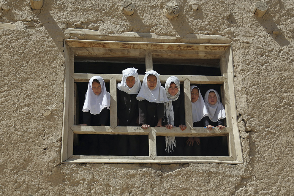 Eleve afgane privesc pe geamul şcolii, în Ghazni, duminică, 15 septembrie 2013.