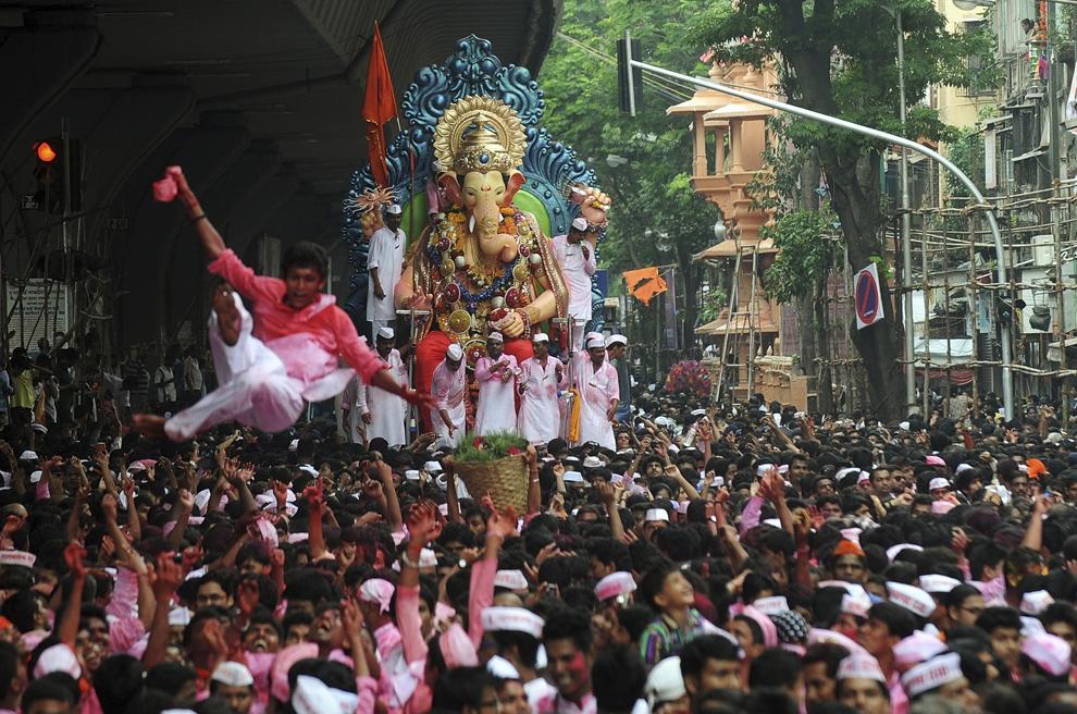 Credincioşi  hindu dansează în timpul procesiunii scufundării statuii cu cap de elefant a zeitaţii indiene Ganesha în marea Arabiei, pe străzile din Mumbai, miercuri, 18 septembrie 2013.