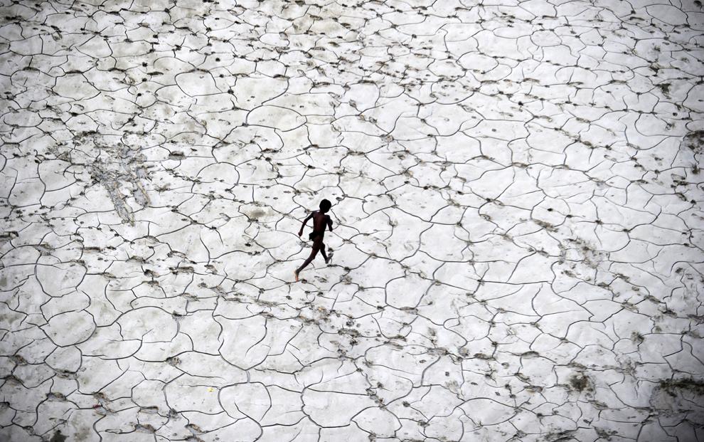 Un copil al străzii se joacă pe fundul secat al unui râu, în Allahabad, vineri, 25 octombrie 2013.