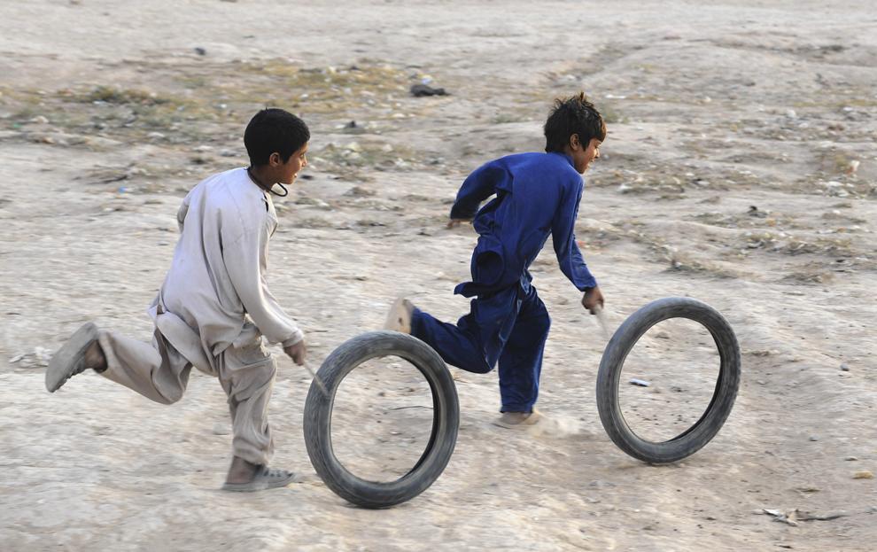 Doi copii afgani se joacă cu cauciucuri uzate în Herat, duminică, 27 octombrie 2013.
