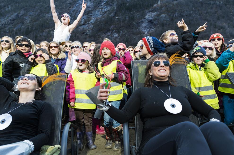 Persoane reacţionează în timpul inaugurării unor oglinzi uriaşe aşezate pe dealurile din apropiere de Rjukan, ce reflectă lumina solară în piaţa centrală, miercuri, 30 octombrie 2013. Locuitorii unui orăşel din Norvegia au inaugurat un sistem ingenios de oglinzi ce aduc lumina naturală în piaţa centrală, ce era învăluită în umbră timp de  6 luni pe an.