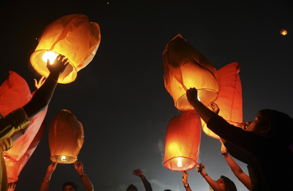 Voluntari indieni lansează lampioane, în Kolkata, India, miercuri, 30 octombrie 2013.