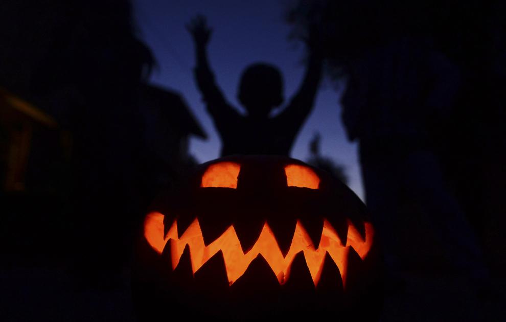 Siluetele unor copii pot fi văzute în spatele unui dovleac decorat pentru Halloween, în Monterey Park, California, miercuri, 30 octombrie 2013.