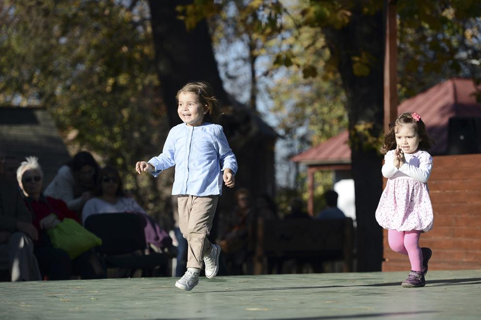 """Doi copii se bucură în timpul unui spectacol de muzică populară organizat cu ocazia Târgului de Sfântul Dumitru, la Muzeul Naţional al Satului """"Dimitrie Gusti"""", în Bucureşti, duminică, 27 octombrie 2013."""