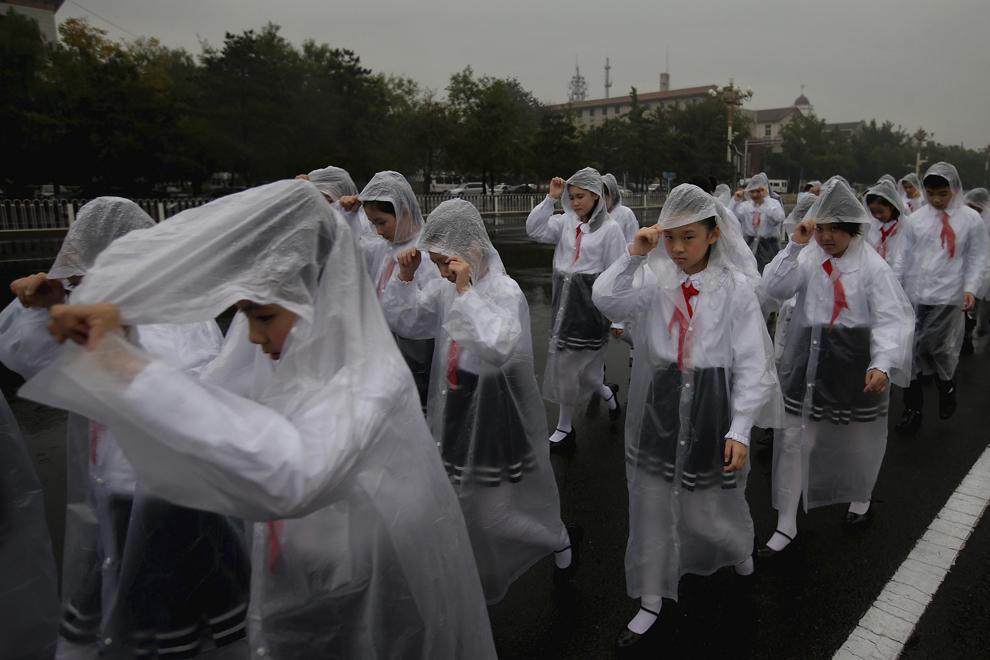 Elevi chinezi se plimbă prin piaţa Tiananmen, înaintea unei ceremonii, în Beijing, China, marţi, 1 octombrie 2013.