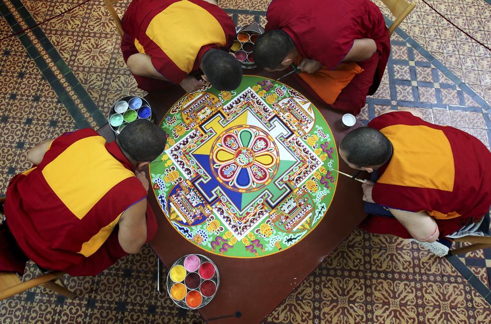 """Călugări tibetani lucrează la o pictură cu nisip """"Chenrezig Sand Mandala"""", în Salisbury, Anglia, joi, 3 octombrie 2013."""