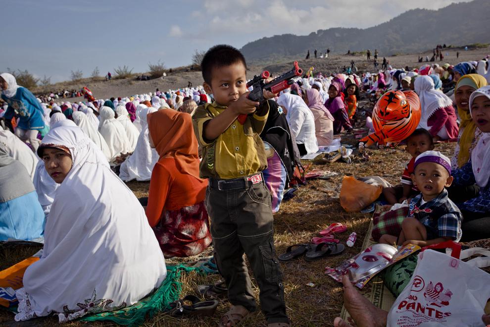 Un băieţel se joacă cu o armă de plastic, în timp ce musulmani indonezieni aşteaptă începerea rugăciunii de Eid al - Adha, în Yogyakarta, Indonezia, marţi, 15 octombrie 2013.