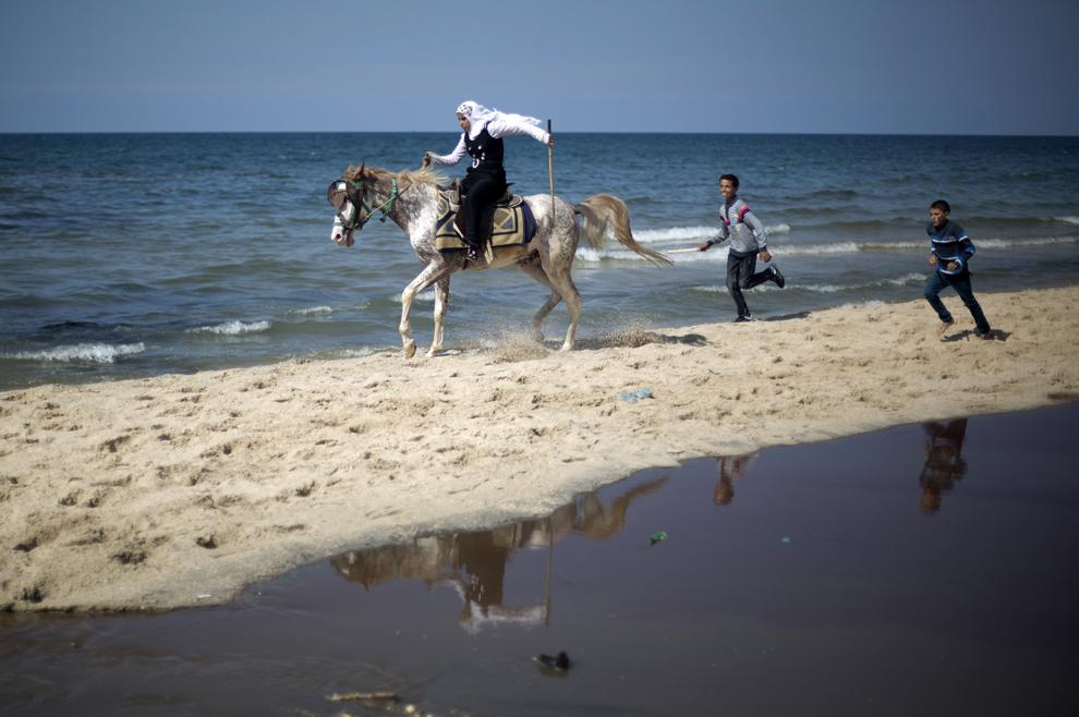 O fetiţă palestiniană călăreşte pe plajă, în cea de-a treia zi a festivalului Eid al-Adha, în Gaza, miercuri, 16 octombrie 2013.
