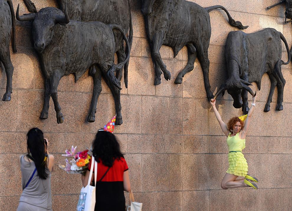 O tânără pozează pentru prietenele sale, în faţa unei sculpturi, în apropiere de Las Ventas, în Madrid, marţi, 8 octombrie 2013.