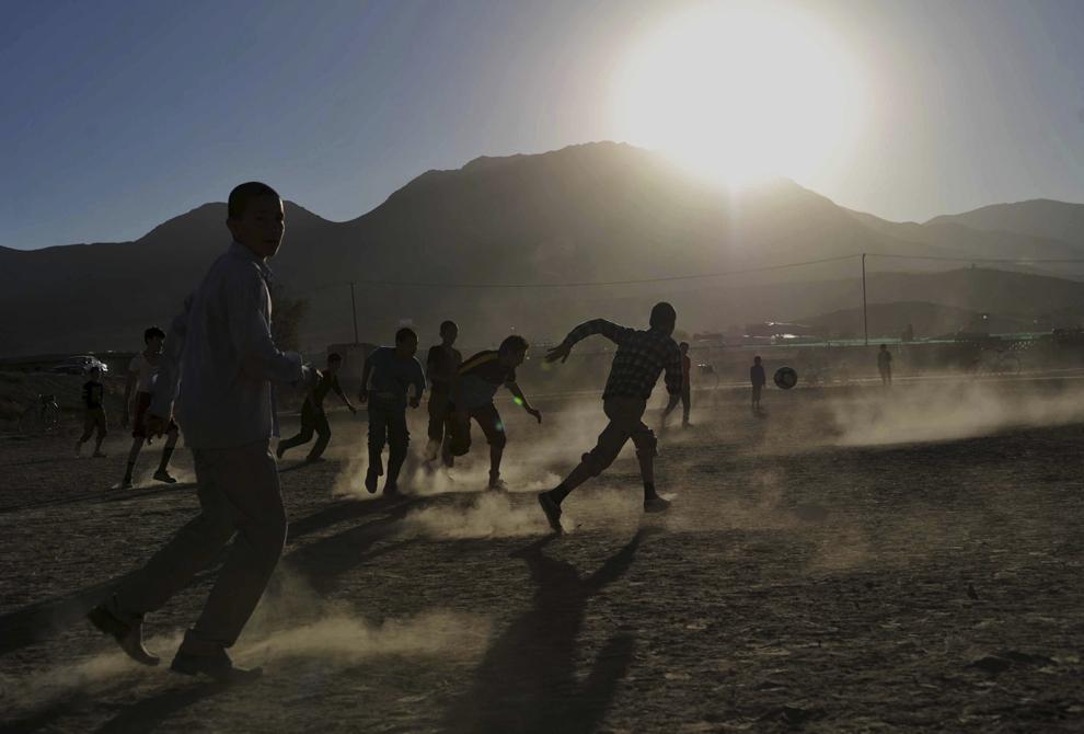 Copii joacă fotbal în faţa ruinelor Palatului Darun Aman, la periferia oraşului Kabul, sâmbătă, 19 octombrie 2013.