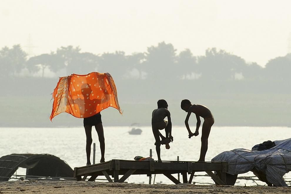 Copii indieni se îmbracă după o baie în râul Sangam din Allahabad, marţi, 29 octombrie 2013.