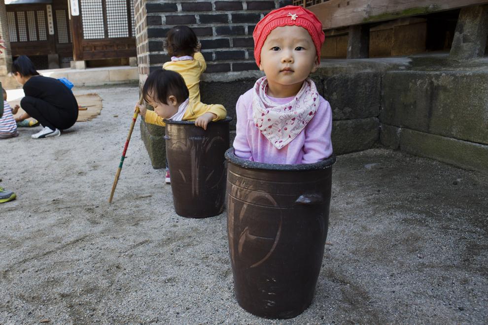"""Jung Ha-yoon, în varsta de  2 ani se joacă cu containere ceramice, în timpul festivalului """"Taste Korea! Korean Royal Cuisine Festival"""", desfăşurat la palatul Unhyeon, în Seul, marţi, 1 octombrie 2013."""