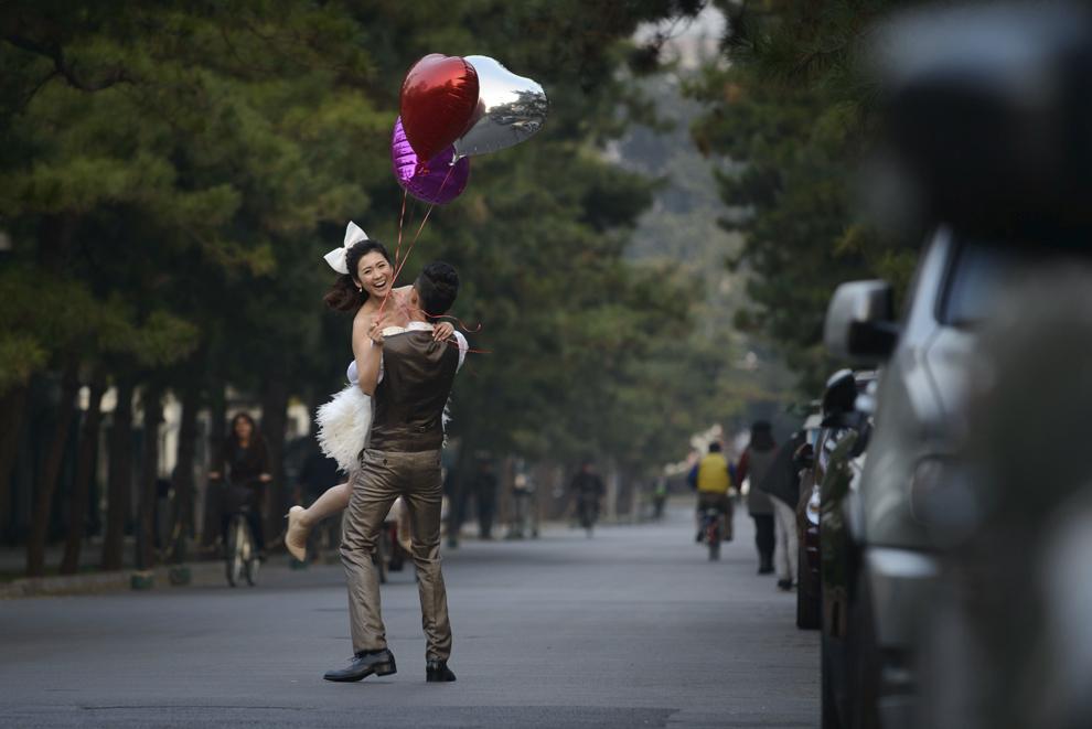 O femeie îmbrăcată în mireasă este ridicată de un bărbat pe o stradă din Beijing, luni, 21 octombrie 2013.