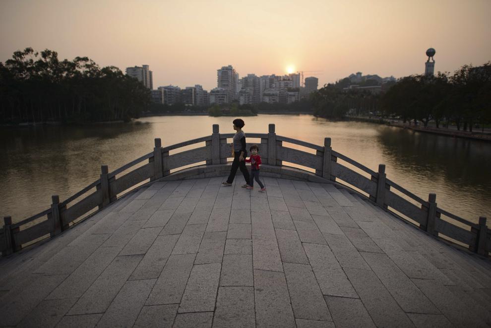 O femeie alături de un copil se plimbă pe un pod dintr-un parc din Fuzhou, provincia Fujian, China, marţi, 22 octombrie 2013.